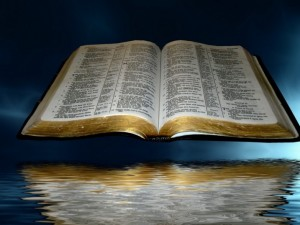 open_bible_over_black_and_blue_clouds_with_reflection